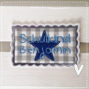 Schulkind Aufnäher Bügelbild Applikation 9x7cm gestickt auf weißen Textilfilz mit graukarierter Baumwolle mit Mittelblau und hellblau sowie Stern