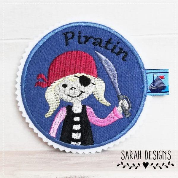 Großer Piratenaufnäher in blau mit beere und rosa sowie schwarz und weiss gestickt auf weissen textilfilz 11cm x 10,5